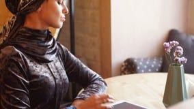 Retrato da menina muçulmana árabe bonita que usa a tabuleta filme