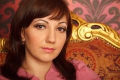 Retrato da menina na camisa vermelha que senta-se na poltrona. Imagens de Stock Royalty Free