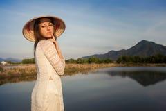 retrato da menina no chapéu vietnamiano contra lagos do país imagens de stock royalty free