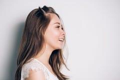 Retrato da menina no perfil A mulher bonita tem uma pele bem arrumado limpa e um cabelo reto longo Retrato do close-up contra a foto de stock