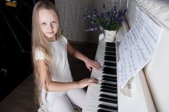 Retrato da menina no vestido branco que joga o piano Imagem de Stock Royalty Free
