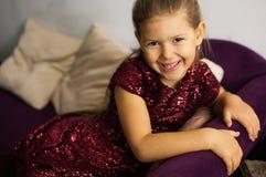Retrato da menina no vestido do bordo no sofá imagens de stock royalty free