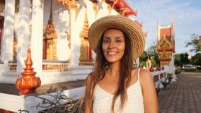 Retrato da menina nova atrativa de sorriso do turista do moderno da raça misturada em Straw Hat com o templo budista tailandês tr video estoque
