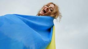 Retrato da menina patriótica nova que guarda a bandeira ucraniana azul e amarela sobre o fundo do céu ao comemorar o visto filme