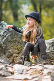 Retrato da menina pensativa em um chapéu negro com orelhas e dia ensolarado da mola preta da roupa fotografia de stock