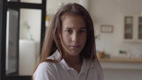 Retrato da menina pequena adorável que olha a câmera que sorri felizmente e que mostra emoções em sua cara em casa carefree filme