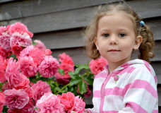 Retrato da menina perto das rosas de florescência Fotos de Stock Royalty Free