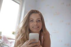 Retrato da menina positiva alegre que senta-se na cama usando a música favorita de escuta dos auriculares espertos do telefone qu imagem de stock royalty free