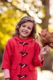 Retrato da menina que guarda as folhas de outono no parque Imagem de Stock