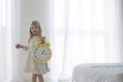 Retrato da menina que guarda o despertador, isolado sobre o branco Fotos de Stock