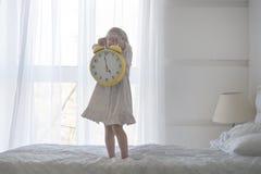 Retrato da menina que guarda o despertador, isolado sobre o branco Foto de Stock