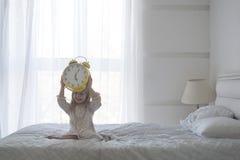Retrato da menina que guarda o despertador sobre sua cabeça, isolado sobre o branco Fotos de Stock Royalty Free