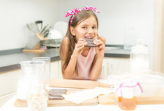Retrato da menina que inclina-se na mesa de cozinha e que come o chocolate Imagem de Stock Royalty Free