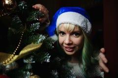 Retrato da menina que olha para fora devido à árvore de Natal Foto de Stock