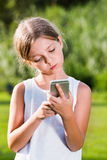 Retrato da menina séria que olha o telefone celular foto de stock