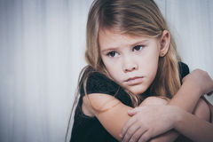 Retrato da menina triste que senta-se perto da janela Fotos de Stock