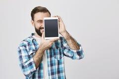 Retrato da metade-cara farpada masculina da coberta do assistente de loja com a tabuleta para anunciá-lo ao sorrir amplamente e a fotos de stock royalty free