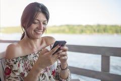 Retrato da moça bonita com o telefone no dia ensolarado no natu imagem de stock royalty free