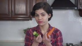 Retrato da moça bonita que mordem e que mastigam primeiramente um pepino grande, e então uma cenoura fresca no fundo de video estoque