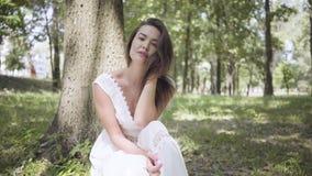 Retrato da moça bonito com o cabelo moreno longo que veste um vestido branco longo da forma do verão que senta-se sob uma árvore  filme