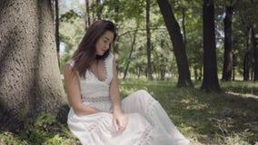 Retrato da moça bonito com o cabelo moreno longo que veste um vestido branco longo da forma do verão que senta-se sob uma árvore  video estoque