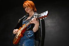 Retrato da moça com a guitarra sobre o fundo preto imagens de stock royalty free