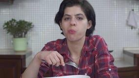 Retrato da moça com um corte de cabelo curto que come a salada fresca deliciosa com tomates e vegetais e que toma o prazer video estoque