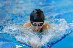 Retrato da moça do close-up nos óculos de proteção e do estilo do curso de borboleta da natação do tampão na associação de água a Fotos de Stock