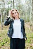 Retrato da moça loura na floresta que endireita seu cabelo imagem de stock royalty free