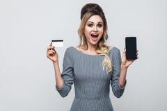 Retrato da moça moderna bonita feliz na posição cinzenta do vestido, guardando o telefone celular e o cartão de crédito com a boc fotografia de stock royalty free