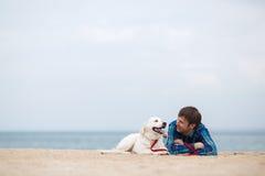Retrato da mola de um homem novo com um cão na praia Fotografia de Stock Royalty Free