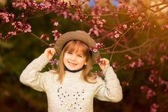 Retrato da mola, menina ador?vel na caminhada do chap?u no jardim da ?rvore da flor no por do sol imagens de stock royalty free