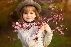 Retrato da mola, menina ador?vel na caminhada do chap?u no jardim da ?rvore da flor no por do sol fotos de stock royalty free