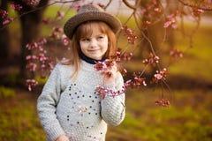 Retrato da mola, menina ador?vel na caminhada do chap?u no jardim da ?rvore da flor no por do sol fotografia de stock royalty free