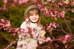 Retrato da mola, menina ador?vel na caminhada do chap?u no jardim da ?rvore da flor fotografia de stock