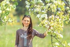 Retrato da mola A menina branca bonita nova em um terno marrom dos esportes está perto dos ramos de florescência de árvores de ma Imagens de Stock Royalty Free