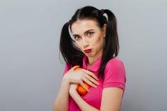 Retrato da morena bonita que guarda a laranja deliciosa suculenta Fundo cinzento foto de stock royalty free