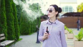 Retrato da mulher à moda com a camisa com cigarro eletrônico Mo lento video estoque