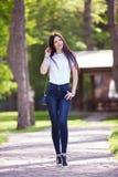 Retrato da mulher à moda feliz bonita na calças de ganga fotos de stock royalty free