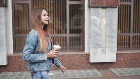 Retrato da mulher à moda feliz nova que anda na cidade e no café bebendo vídeos de arquivo