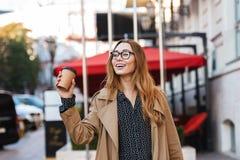 Retrato da mulher à moda que bebe o café afastado ao andar através da rua da cidade fotografia de stock