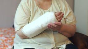 Retrato da mulher adulta com braço quebrado, sua mão do close-up em um molde filme