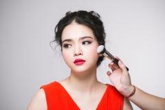 Retrato da mulher adulta nova asiática atrativa que aplica o ruge Imagem de Stock