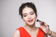 Retrato da mulher adulta nova asiática atrativa que aplica o ruge Fotografia de Stock Royalty Free