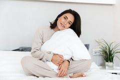 Retrato da mulher adulta 30s que senta-se na cama com descanso branco, ao descansar em casa imagens de stock royalty free