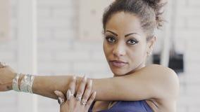 Retrato da mulher afro-americana nova, que está esticando seus muscules do ombro no gym filme