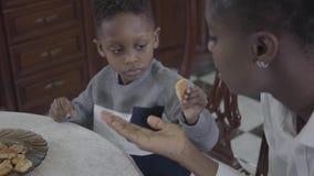 Retrato da mulher afro-americano atrativa que senta-se com seu filho pequeno pela tabela que joga cookies na placa vídeos de arquivo