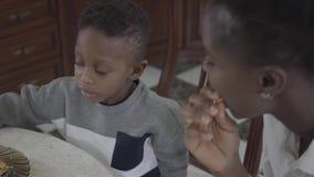 Retrato da mulher afro-americano atrativa que senta-se com seu filho pequeno pela tabela que joga junto com cookies vídeos de arquivo