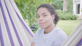 Retrato da mulher afro-americano de sorriso nova bonito que senta-se na rede, relaxando no jardim, texting sobre video estoque