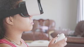 Retrato da mulher afro-americano que veste nos auriculares da realidade virtual usando o manche que senta-se na poltrona em casa vídeos de arquivo